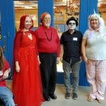 Five people, one in a wheelchair, wearing Halloween costumes get together for a picture.