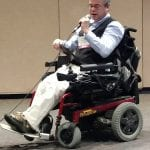 Person in wheelchair holds a microphone and speaks to audience.