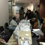 People check in at the registration table outside the event.