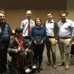 Six attendees, one in a wheelchair, group together for a photo at front of the room.