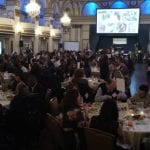 A wide shot of the ballroom as people have dinner.