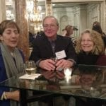 Three people seated at a table take a picture while having refreshments.