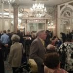 People gather in the ballroom talking and having refreshments before the event begins.