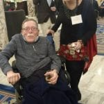 A person with a drink in their hand takes a photo with a person in a wheelchair.