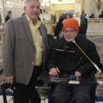 Two people smile for a photo. One on the right is seated in a wheelchair.