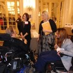 People, two in wheelchairs and two standing, speaking to each other.