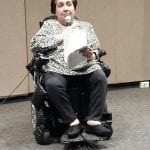 Person in a black and white shirt seated wheelchair holds a microphone and hold papers as they speak.