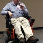 Person in a wheelchair wearing a blue shirt and khaki pants speaks into a microphone to an audience.