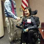 Person holds microphone for person in wheelchair to speak.