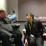 Two people in wheelchairs speaking to each other.