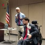 Person standing with microphone speaks with person sitting in wheelchair.