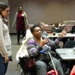 A person in a black and purple sweater seated in a wheelchair speaks itno a wheelchair while a woman in a white sweater stands nearby.