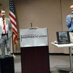 A person in a blue shirt and purple tie speaks into a microphone next to a person in a gray suit and red tie. In between the two are a podium with a white Boston Center for Independent Living sign and a table with clear awards and a memorial plaque.