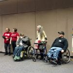 A person in a blue shirt and purple tie addresses a group of people standing next to him. Two people are wearing red Boston Center for Independent Living t-shirts, two people are in wheelchairs and two are standing holding walkers.