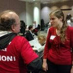 A person in a red BCIL t-shirt speaks to another person.
