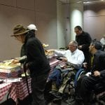 A group of people, two in power wheelchairs help themselves to a catered dinner.
