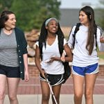 A trio of students are talking among themselves as the student in the middle uses a white cane to walk.