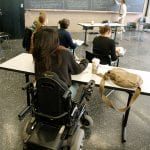 Five people sit in a lecture style classroom. Four of the people are seated in desks while one, seated in a wheelchair, sits behind them with a messenger bag on the table.