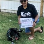 A Caucasian person wearing a black ADA 30 t-shirt kneels next to a dog and holds a sign that read AN ACCESSIBLE WORLD IS BETTER FREE PUBLIC TRANSPORTATION!