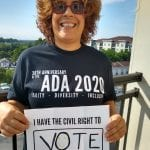 A Caucasian person wearing a black ADA 30 t-shirt holds a sign that reads I HAVE THE CIVIL RIGHT TO VOTE.