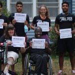 A group of people, four standing, one in a wheelchair and one in an electric scooter, hold up signs for the ADA event.