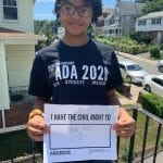 An African American person wearing a black ADA 30 t-shirt holds a sign that reads I HAVE THE CIVIL RIGHT TO BE ME.