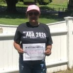 A Caucasian person wearing a black ADA 30 t-shirt holds a sign that read AN ACCESSIBLE WORLD IS BETTER FREE PUBLIC TRANSPORTATION!