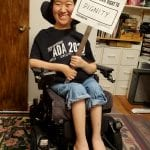 An Asian person sitting in a wheelchair wearing a black ADA 30 t-shirt holds a sign that reads I HAVE THE CIVIL RIGHT TO DIGNITY.
