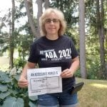 A Caucasian person wearing a black ADA 30 t-shirt holds a sign that reads AN ACCESSIBLE WORLD IS ACCESSIBLE TO ALL.