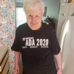 A Caucasian person wearing a black ADA 30 t-shirt smiles for a photo.