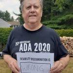 A person wearing a black ADA 30 t-shirt holds a sign that reads DISABILITY DISCRIMINATION IS WRONG.