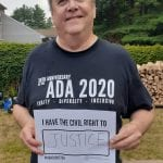 A Caucasian person wearing a black ADA 30 t-shirt holds a sign that reads I HAVE THE CIVIL RIGHT TO JUSTICE.