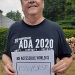 A person wearing a black ADA 30 t-shirt holds a sign that reads AN ACCESSIBLE WORLD IS DIVERSE.