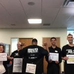 Five people wear black ADA30 t-shirts and hold up sheets of paper.