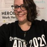 A person wearing a black ADA 30 t-shirt smiles for a photo in front of a bulletin board.