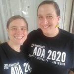 Two Caucasian people wearing black ADA 30 t-shirts take a group photo.