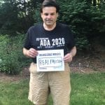 A Caucasian person wearing a black ADA 30 t-shirt holds a sign that reads AN ACCESSIBLE WORLD IS REAL FREEDOM.