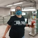 A Caucasian person wearing a black ADA 30 t-shirt and blue facial mask smiles for a photo while holding an iced coffee.
