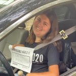 A person sitting in a car wearing a black ADA 30 t-shirt holds a sign that reads AN ACCESSIBLE WORLD IS ON THE MOVE!