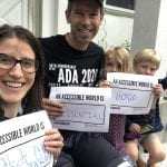 A Caucasian family wearing black ADA 30 t-shirt hold signs that reads AN ACCESSIBLE WORLD IS ESSENTIAL, GOOD and HAPPY.