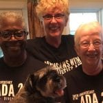 Two Caucasian people and an African American person wearing black ADA 30 t-shirts smiles for a group photo with a puppy in the foreground.