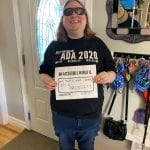 A person wearing a black ADA 30 t-shirt and sunglasses holds a sign that reads AN ACCESSIBLE WORLD IS NOT JUST A NICE IDEA, IT'S A NECESSITY.