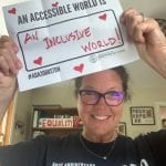 A Caucasian person wearing a black ADA 30 t-shirt holds a sign that reads AN ACCESSIBLE WORLD IS AN INCLUSIVE WORLD.