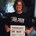 A Caucasian person wearing a black ADA 30 t-shirt holds a sign that read AN ACCESSIBLE WORLD IS MY RIGHT.