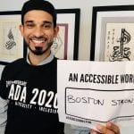 A Middle Eastern person wearing a black ADA 30 t-shirt holds a sign that read AN ACCESSIBLE WORLD IS BOSTON STRONG.