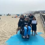 Four Caucasian people, one in a wheelchair, smile for a group photo on a beach wearing black 30 ADA t-shirts.