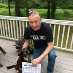 A Caucasian person kneeling with a dog and wearing a black ADA 30 t-shirt holds a sign that reads AN ACCESSIBLE WORLD IS ONE MADE FOR ALL OF US.