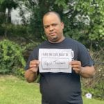 An African American person holds up a sign saying I HAVE THE CIVIL RIGHT TO EQUAL TREATMENT.