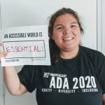 A Caucasian person wearing a black ADA 30 t-shirt holds a sign that read AN ACCESSIBLE WORLD IS ESSENTIAL!