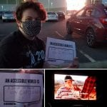 A person wearing a black ADA 30 t-shirt holds a sign that read AN ACCESSIBLE WORLD IS A DRIVE-IN WITH CAPTIONS!